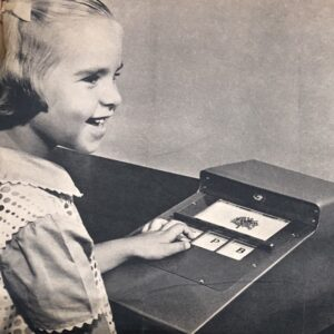 Smiling girl using a teaching machine.